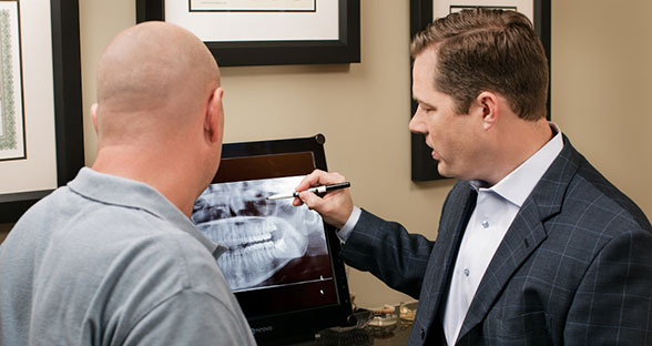 Dr. Wilson (oral surgeon) having a conversation with a patient in one of his oral surgery offices in Phoenix, Casa Granda, Mesa, and Gilbert.